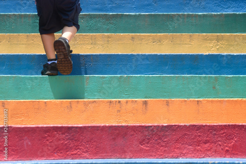 Obraz Lower part of a boy in casual shoe walking up outdoor colorful stair,children lifestyle successful concept - fototapety do salonu