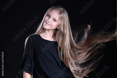 Portrait of a blonde girl with long hair on a black background. Emotional portrait.The girl shows different emotions on the face. Plays with long hair.