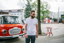 Handsome Hipster Man In Sunglasses Walking Along The Street. White T-shirt.