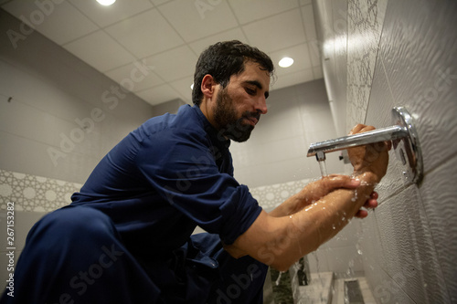 """A Muslim man cleans his arm during a process known as """"wudu"""" ahead of"""