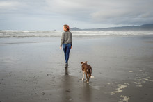 Young Woman And Her Dog Walking On The Beach In Northern California