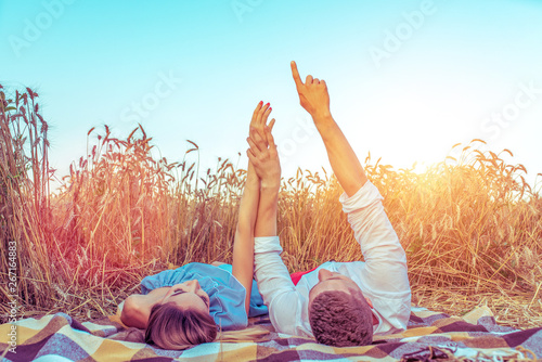 Foto auf AluDibond Licht blau A young couple, man woman, in wheat field summer, lie on rug. Hand gestures indicate stars. Concept love, date, emotion, tenderness, warmth, care, romance. Happiness hugs lovers, young family.