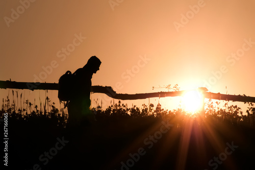Aluminium Prints Red Portrait of an man with backpack on backlight background. Rural scene on blacklight. Silhouette of young tourist in village going with backpack on green summer morning. Copy space