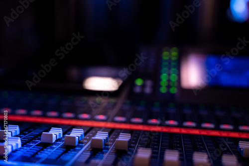 Fototapeta  Close up of faders on an audio mixing console in a concert venue
