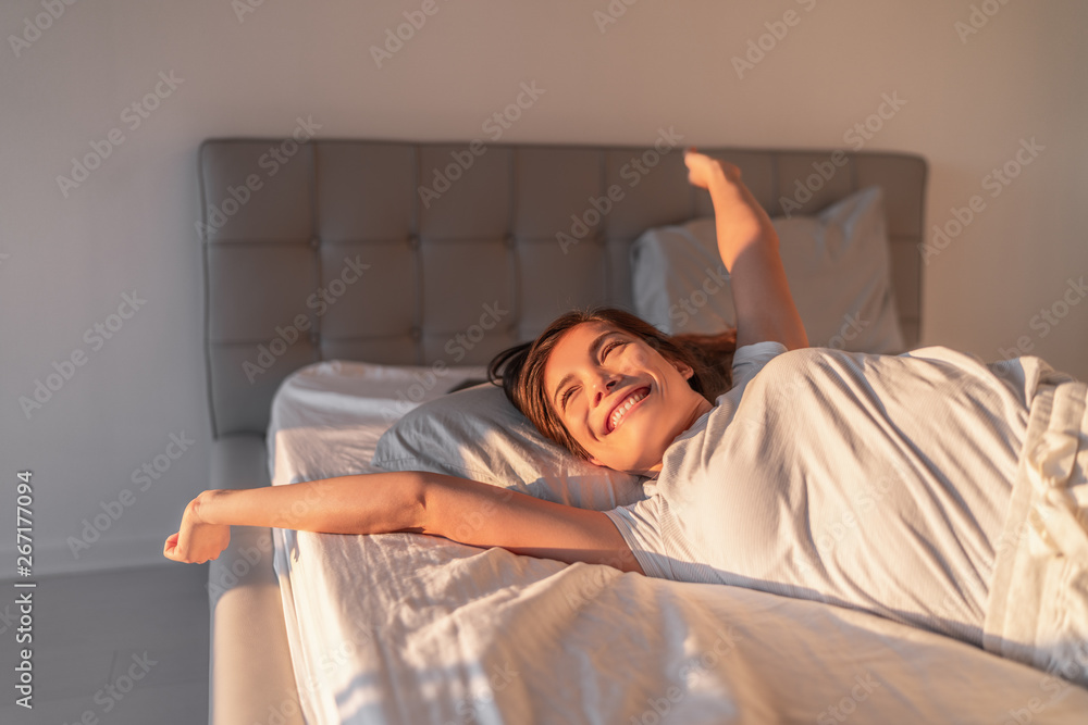 Fototapeta Happy girl waking up in the morning sunshine looking at sunrise sun in window excited to enjoy the day. Wake up energetic Asian woman lying in bed well rested from a good night sleep.