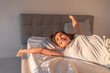canvas print picture - Happy girl waking up in the morning sunshine looking at sunrise sun in window excited to enjoy the day. Wake up energetic Asian woman lying in bed well rested from a good night sleep.