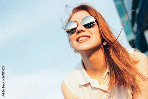 Poster Gypsy Positive beautiful happy red haired girl in the mirror sunglasses on blue sky background, summer sunset time