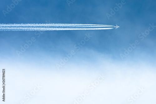 Fotografija  Airplane flying, contrails in the blue sky.