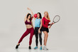 Group of fit attractive woman friends standing together with different sport equipment on gray background. different sports