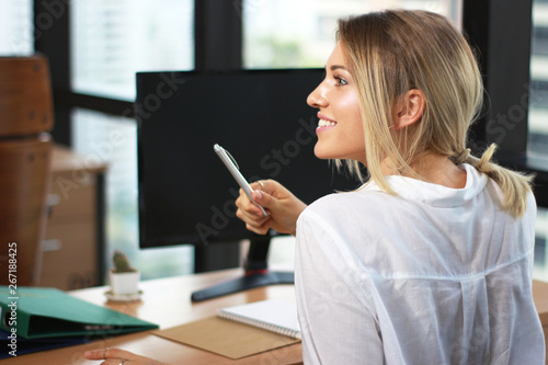 Portrait of a businesswoman working with pen in hands in modern office building Fototapete