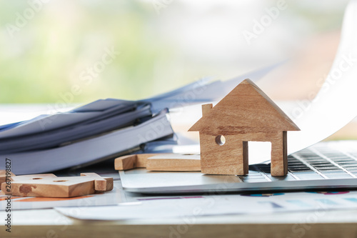 Home model for loan real estate to buy new for family or property mortgage investment concept: Wooden house models on laptop computer with chart report documents,wealth management for agency online Canvas Print