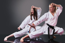 Two Beautiful Young Female Karate Players Doing Kata On The Gray Background