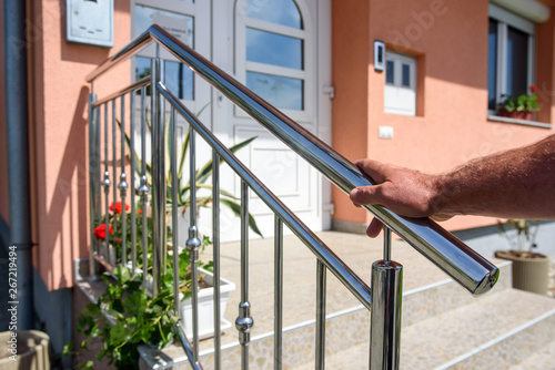 obraz lub plakat chrome fence on staircase. hand holds stainless steel fence