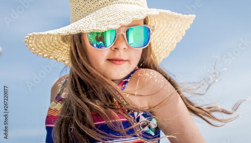 Dziewczyna w kapeluszu na plaży ma wiatr we włosach