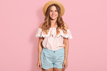 Happy girl posing in straw hat, rose summer blouse and blue short. Beautiful woman has charming smile, being in good mood, expresses happyness, looking directly at camera, standing isolated on pink.