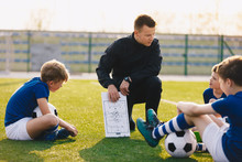 Football Coach Coaching Children. Soccer Football Training Session For Children. Young Coach Teaching Kids On Football Field. Football Tactic Education. Coach Explains The Strategy Of The Game