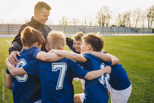 Fotografiet  Group Of Children In Soccer Team Celebrating With Coach