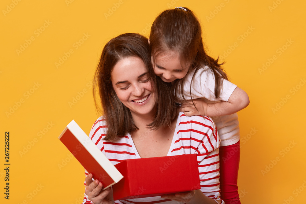 Fototapety, obrazy: Family, child, holiday and Mother's Day concept. Smiling young woman in striped shirt sitting with her toddler daughter and opening red box, present for holiday, liitle girl in t shirt and trousers.