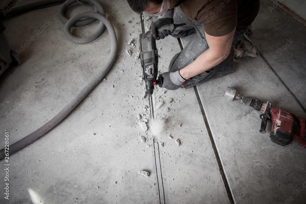 Fototapety, obrazy: Bauarbeiter stemmt Schlitze in den Betonboden auf der Baustelle