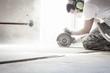 canvas print picture - Bauarbeiter schneidet in Beton mit großer Flex auf der Baustelle