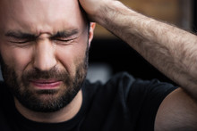 Depressed Bearded Man Crying With Closed Eyes And Holding Hand On Head