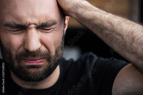 Photo depressed bearded man crying with closed eyes and holding hand on head
