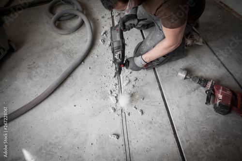 Photo Bauarbeiter stemmt Schlitze in den Betonboden auf der Baustelle