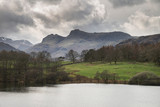 Mody landscape image of Loughrigg Tarn in UK Lake District during dramatic evening in Spring - 267228224