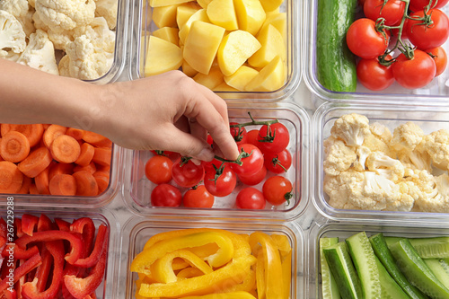 Fotografia  Woman putting tomatoes into box and containers with raw vegetables, closeup