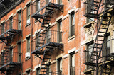 Fototapeta Nowy Jork - Close-up view of New York City style apartment buildings with emergency stairs along Mott Street in Chinatown neighborhood of Manhattan, New York, United States.