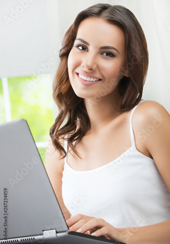 Fototapety, obrazy: Cheerful beautiful girl using laptop, indoors