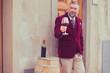 Leinwandbild Motiv Confident elegant dressed man with glass of red wine standing outdoors