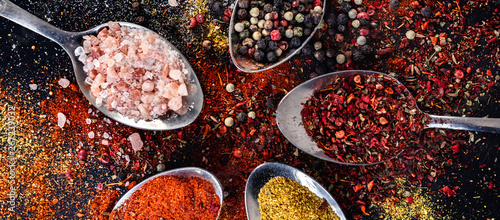 Obraz na plátně Spoons with different indian spices scattered on background table, peppercorn pa