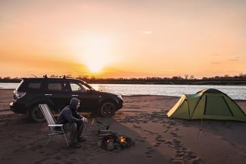 Man at campfire at sunset