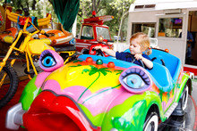 Adorable Little Toddler Girl Riding On Funny Car On Roundabout Carousel In Amusement Park. Happy Healthy Baby Child Having Fun Outdoors On Sunny Day. Family Weekend Or Vacations