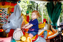 Adorable Little Toddler Girl Riding On Animal On Roundabout Carousel In Amusement Park. Happy Healthy Baby Child Having Fun Outdoors On Sunny Day. Family Weekend Or Vacations