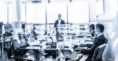 Successful team leader and business owner leading informal in-house business meeting. Businessman working on laptop in foreground. Business and entrepreneurship concept. Blue toned grayscale.
