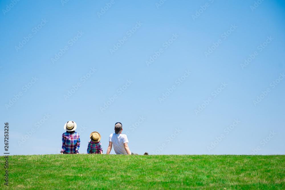 Fototapeta 草原で座るファミリー
