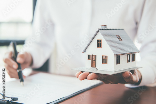House model with real estate agent and customer discussing for contract to buy house, insurance or loan real estate background.