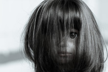 The Face Of A Creepy Girl Doll With Long Hair. Doll Face Closed By Hairs