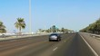 Driving on Abu Dhabi city highway, approaching the Aldar headquarters building, a famous landmark in the city