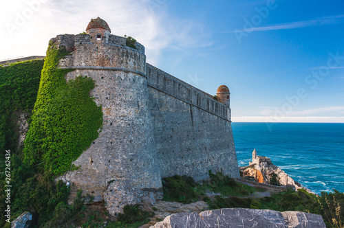 Fotografie, Obraz  Andrea Doria Castle in Porto Venere, La Spezia, Italy, covered in green ivy, looking fairy tale like, overlooking the Gulf of Poets and the stunning Church of Saint Peter (Chiesa di San Pietro)