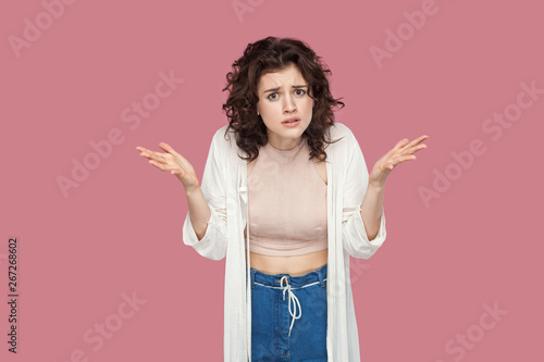 Canvastavla  What do you want? Portrait of angry brunette young woman with curly hairstyle in casual style standing, looking at camera with raised arms and asking