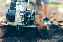 Close Up Photo Of Young Farmer Gardener Cultivate Ground Soil Rototiller , Tiller Tractor, Cutivator, Miiling Machine, Prepare For Planting Crop, Spring. Modern Farming, Technology Agriculture