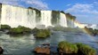Panoramic shot of Iguazu Falls with a rainbow above the water flowing, on a bright sunny day