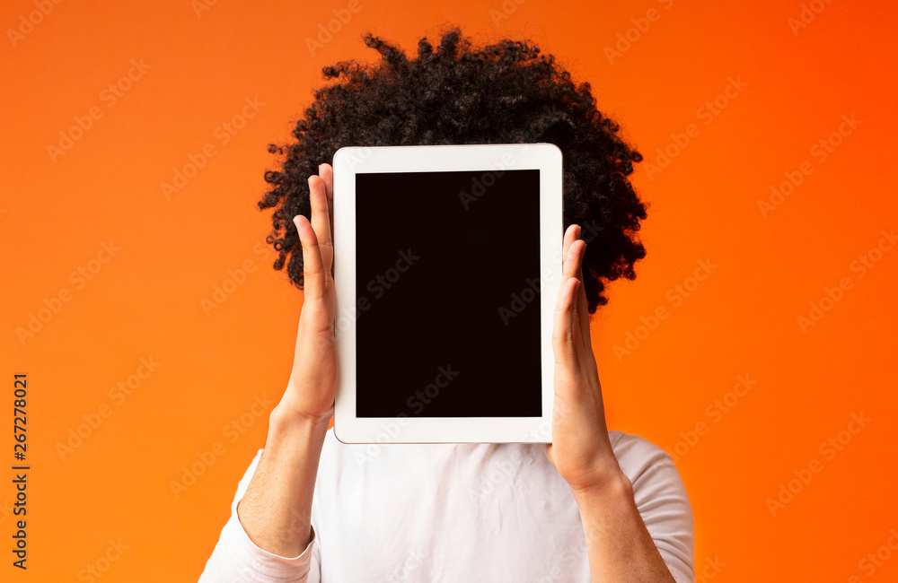 Fototapety, obrazy: Young man hiding his face behind digital tablet