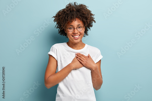 Photo Indoor shot of happy dark skinned lady swears or promises something, holds hands
