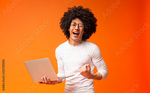 Платно African-american guy enjoying achievement with laptop and screaming