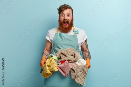 Horizontal shot of desperate redhead man shouts with annoyance, holds basin with pile of dirty laundry, has tattoos on arms, wears casual t shirt and apron, isolated over blue wall Canvas Print