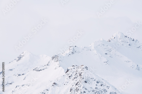 Fotografia Snow-covered mountain peaks against the cloudy sky